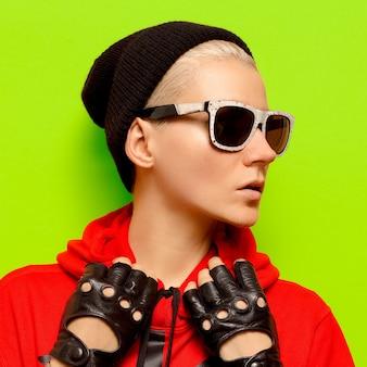 Ragazza alla moda in accessori autunnali. cappello, guanti e occhiali da sole. malloppo, festone