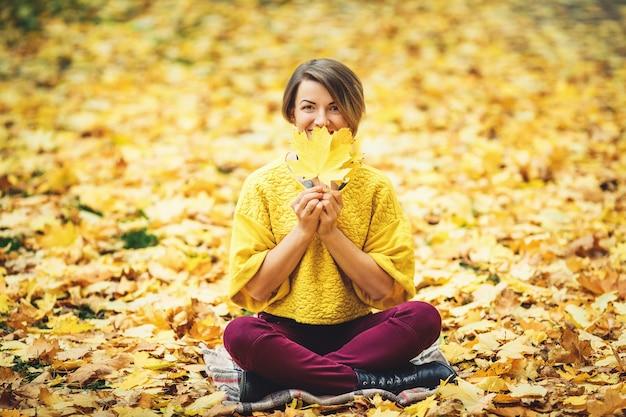 Ragazza alla moda in autunno si siede sull'erba e chiude la bocca con foglie gialle.