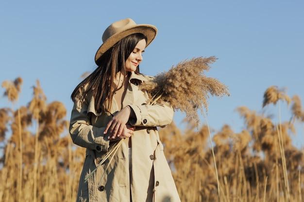 Ragazza alla moda in un trench beige e un cappello in campagna su uno sfondo di canne secche e cielo blu