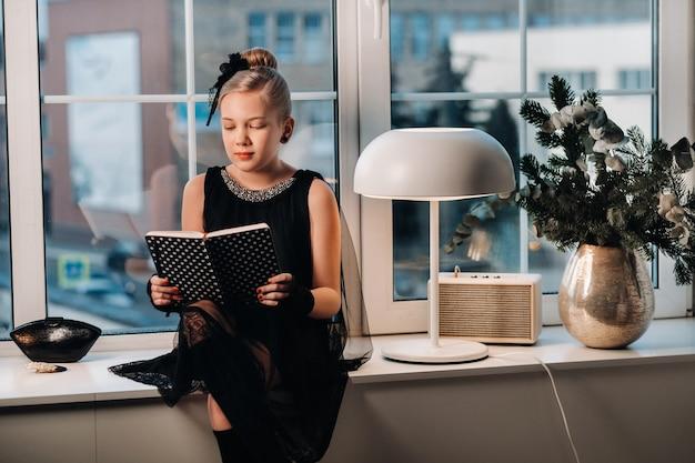 Una ragazza alla moda in un vestito nero si siede sul davanzale della finestra vicino alla finestra con un libro in mano.