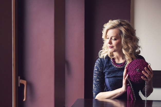 Ragazza alla moda in vestito nero con borsa e collana lavorate a maglia viola fatte a mano.