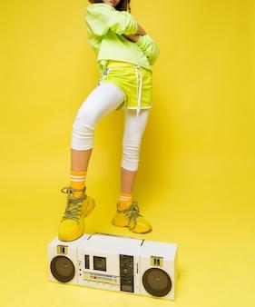 Una ragazza alla moda con una maglietta verde chiaro e pantaloncini, leggings bianchi, scarpe da ginnastica gialle e calzini ha messo il piede su un registratore retrò. foto verticale