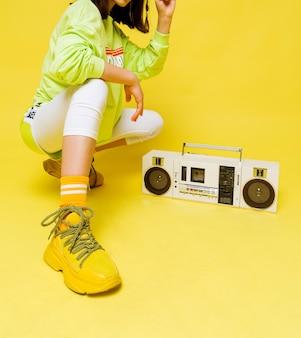 Ragazza alla moda in una maglietta verde chiaro brillante e pantaloncini, leggings bianchi, scarpe da ginnastica gialle e calzini si siede e posa vicino a un registratore retrò. foto verticale