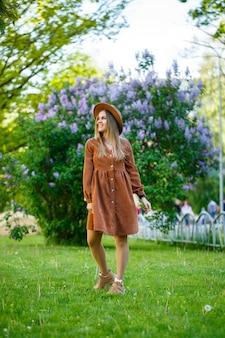 Ragazza alla moda con un cappello marrone e un vestito leggero su uno sfondo di cespugli lussureggianti lilla. giovane donna con un sorriso sul viso in una soleggiata giornata estiva cammina nel parco