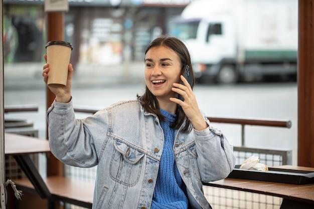 Ragazza alla moda in stile casual parla al telefono con il caffè in mano e sta aspettando qualcuno