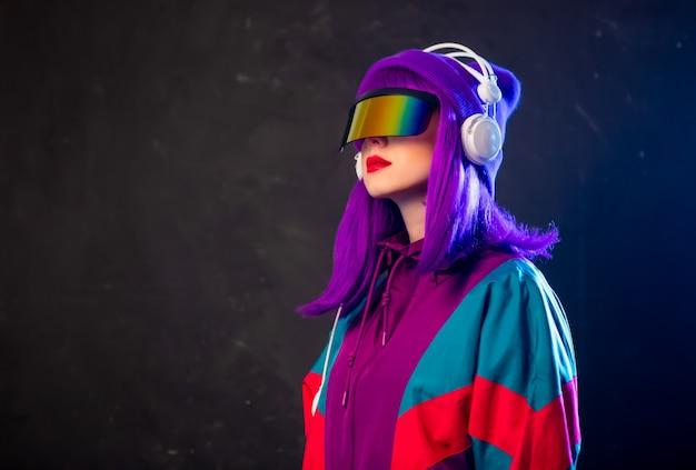 Ragazza alla moda in occhiali cyber punk e tuta con le cuffie sulla parete scura