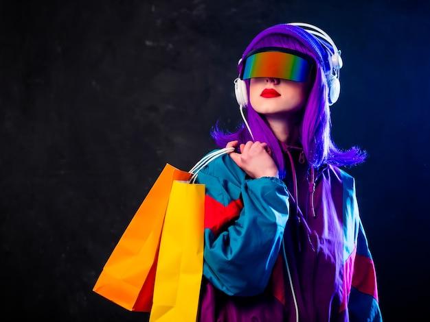 Ragazza alla moda in occhiali cyber punk e tuta con borse della spesa e cuffie sulla parete scura