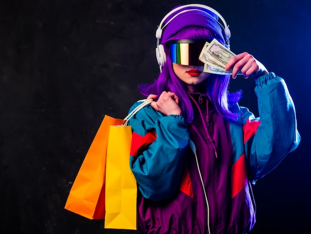 Ragazza alla moda in occhiali cyber punk e tuta con borse della spesa e soldi sulla parete scura
