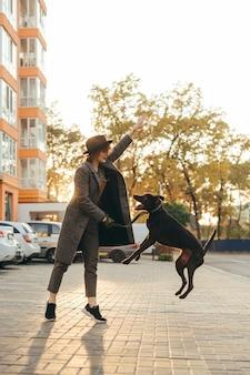 Ragazza alla moda sta addestrando un cucciolo sulla strada di sera