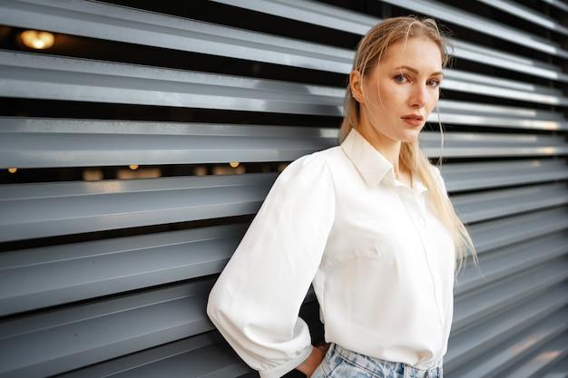 Ragazza alla moda in jeans e camicetta di cotone bianca in posa vicino al muro grigio