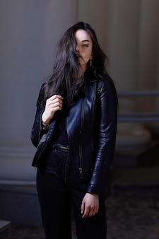 Ragazza alla moda in una giacca di pelle e trucco da sera, in piedi sulla strada della città di notte