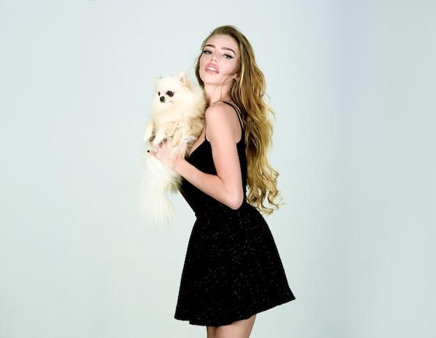Ragazza alla moda in tubino nero con il cane in mano. donna con cucciolo. bella donna con spitz di pomerania. animale di moda. razza canina. la ragazza tiene il piccolo cane. isolato.