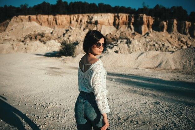 Ragazza alla moda che posa nel grande canyon all'aperto
