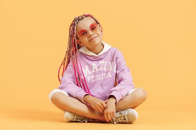 Ragazza alla moda in occhiali arrotondati con i dreadlocks rosa in posa su uno sfondo giallo