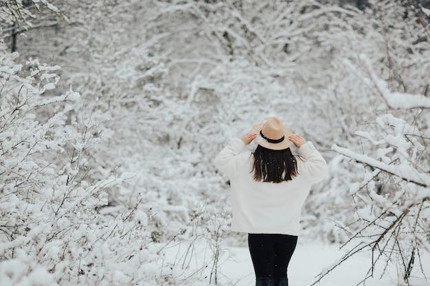 Ragazza alla moda in piedi tra gli alberi innevati nella foresta invernale e godersi il tempo nevoso.