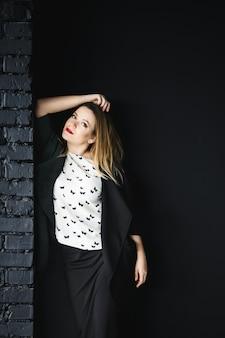 La ragazza alla moda si trova vicino alla parete