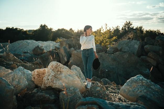 La ragazza alla moda sta sulle pietre in cava all'aperto