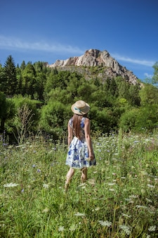 Ragazza alla moda in cappello di paglia che viaggiano sulle montagne soleggiate.