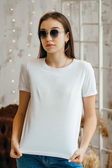Ragazza alla moda indossando t-shirt bianca e occhiali da sole in posa in studio