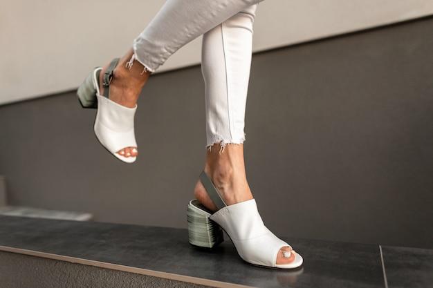 Ragazza alla moda in jeans bianchi e scarpe estive alla moda cammina per strada. avvicinamento.
