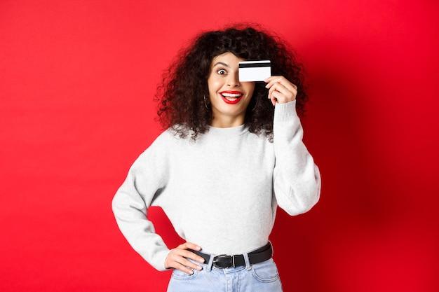 Elegante ragazza con i capelli ricci che mostra la carta di credito in plastica sopra gli occhi e sorridente, in piedi contro il muro rosso.