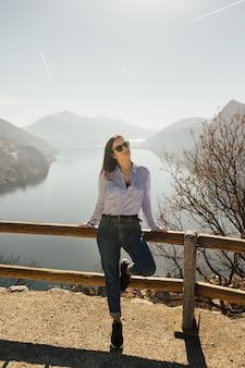 Ragazza alla moda con gli occhiali e la maglietta blu in cima alla collina con il lago di lugano in svizzera sullo sfondo.