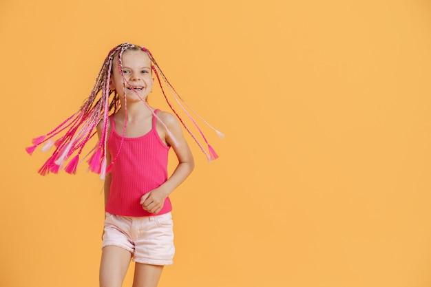 Ragazza alla moda con i dreadlocks rosa in posa su uno sfondo giallo
