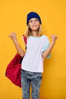 Ragazza alla moda con uno zaino da scuola rosso che gesticola con le mani