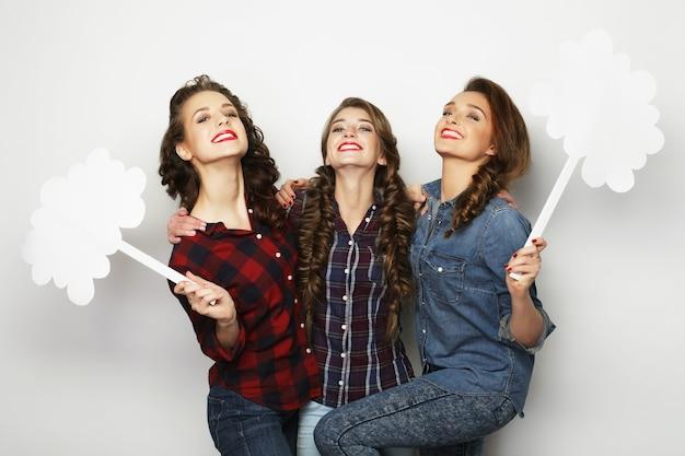 Migliori amiche di ragazze alla moda che tengono carta bianca sul bastone