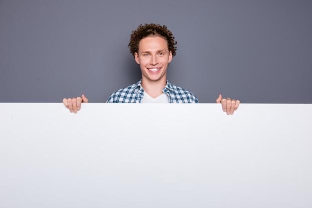 Elegante uomo felice con capelli ondulati in camicia a scacchi casual che tiene scheda promozionale bianca