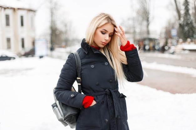 Ragazza alla moda glamour giovane modello in un cappotto invernale di moda con una borsa a piedi in città
