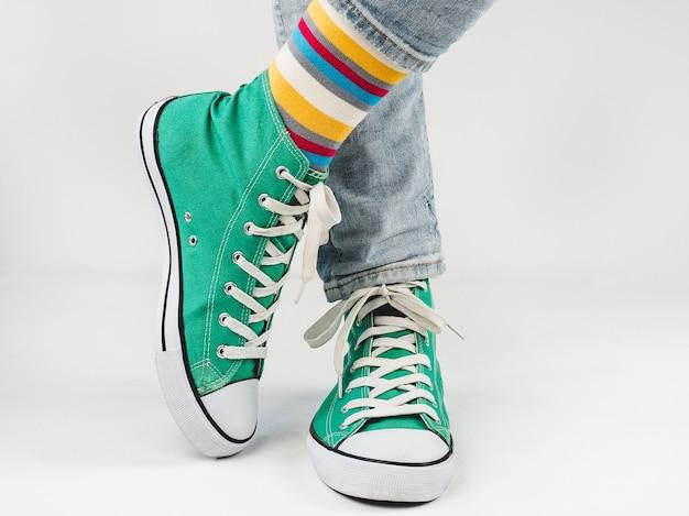 Eleganti scarpe da ginnastica verdi e calzini divertenti su una superficie bianca. concetto di moda, bellezza e buon umore