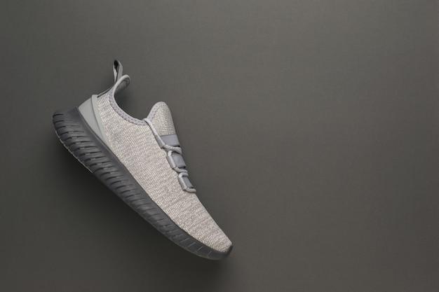 Eleganti scarpe da ginnastica grigie su sfondo grigio scuro. stile di vita sportivo.
