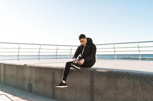 Ragazzo alla moda 20s in tuta nera che si allaccia i lacci delle scarpe mentre corre in riva al mare lungo il molo durante l'allenamento mattutino