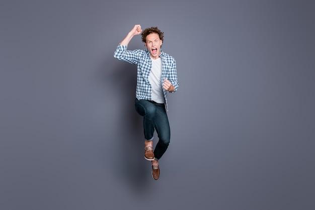 Ragazzo alla moda in una camicia a scacchi blu in posa contro il muro grigio