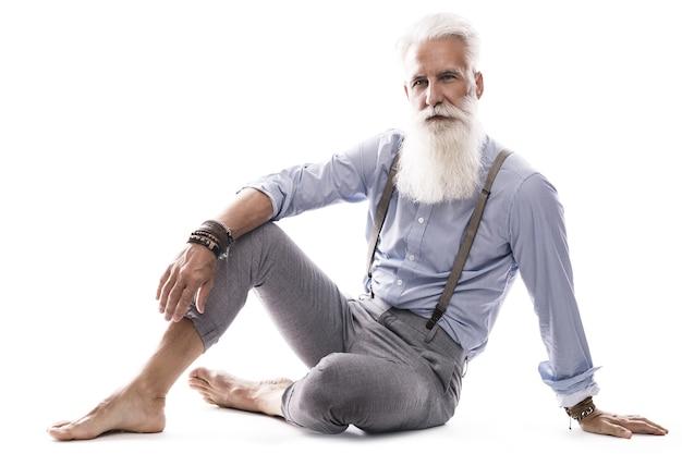 Modello maschio invecchiato alla moda e bello che posa sul bianco