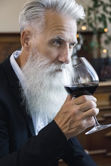 Uomo anziano barbuto elegante e bello che beve vino rosso