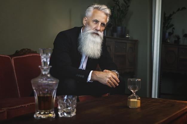 Uomo anziano barbuto elegante e bello che beve whisky