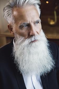 Uomo anziano barbuto elegante e bello che propone nello studio