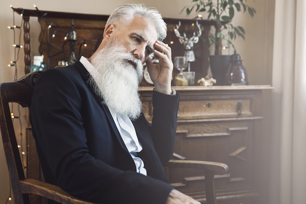 Uomo anziano barbuto elegante e bello che posa in studiosm