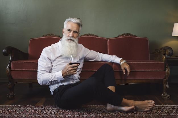 Uomo anziano barbuto elegante e bello che si siede sul pavimento e che beve vino rosso