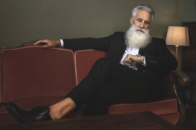 Uomo anziano barbuto elegante e bello che si siede sul divano