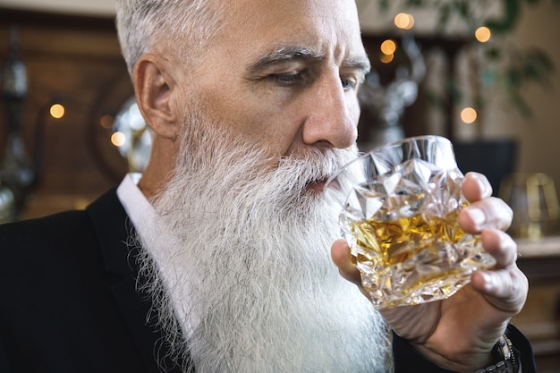 Uomo anziano barbuto elegante e bello con un bicchiere di whisky