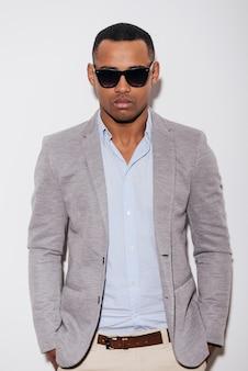 Bello alla moda. fiducioso giovane africano in occhiali da sole che si tiene per mano in tasca