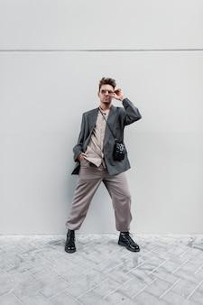 Elegante modello di bel ragazzo con occhiali da sole in una giacca alla moda con camicia, borsa, pantaloni e scarpe da ginnastica si erge su uno sfondo grigio