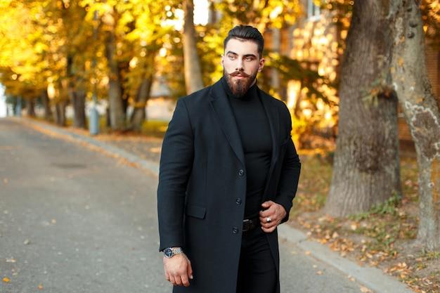 Uomo bello alla moda in un cappotto nero che cammina all'aperto in una giornata di sole autunnale