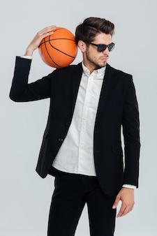 Elegante bell'uomo in abito nero e occhiali da sole che tiene la palla da basket sulla spalla sopra il muro grigio
