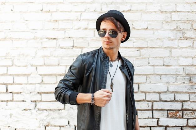 Elegante bell'uomo con occhiali da sole e un cappello nero in una giacca di pelle vicino al muro di mattoni d'epoca
