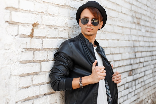Uomo bello alla moda con occhiali da sole in camicia bianca e giacca nera in posa vicino al muro di mattoni