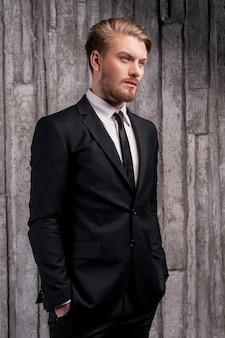 Bello alla moda. vista laterale di un bel giovane in abiti da cerimonia che si tiene per mano in tasca e distoglie lo sguardo